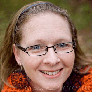 Picture of a white woman with long blond hair held back with a headband. She is wearing glasses.