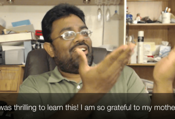 "A South Asian Indian man with glasses and a beard is signing in sign language with his two hands raised. The caption reads: ""It was thrilling to learn this! I am so grateful to my mother!"""