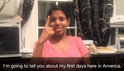 """A South Asian woman in a pink shirt using sign language. A caption below the photo reads: """"I'm going to tell you about my first days here in America."""""""
