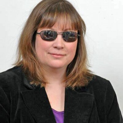 White woman with long brown hair wearing dark sunglasses. She has a black blazer on with a purple t-shirt on the inside.