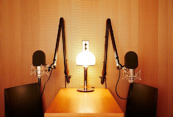 Picture of a small wooden table with two black chairs, one on the left and one on the right. At the center of the table is a small lamp and two swinging arms holding microphones for recording.