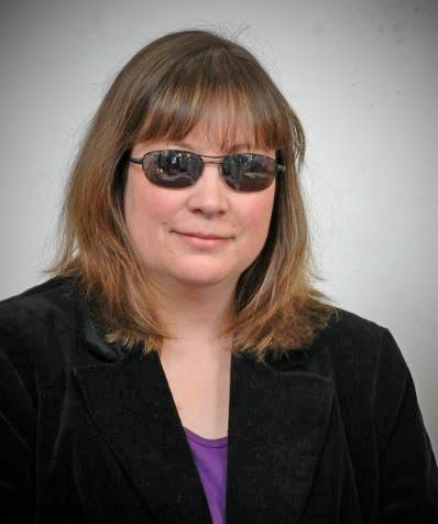 Middle aged white woman with shoulder-length brown hair. She has sunglasses on with reflective lenses and a black blazer and purple t-shirt