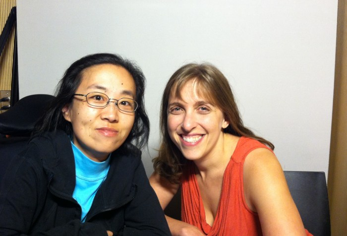 Asian American woman on the left side in a wheelchair, she is wearing glasses and wearing a black hoodie. On her right is a white woman with long blonde-brown hair wearing an orange tank top. Both are smiling at the camera.