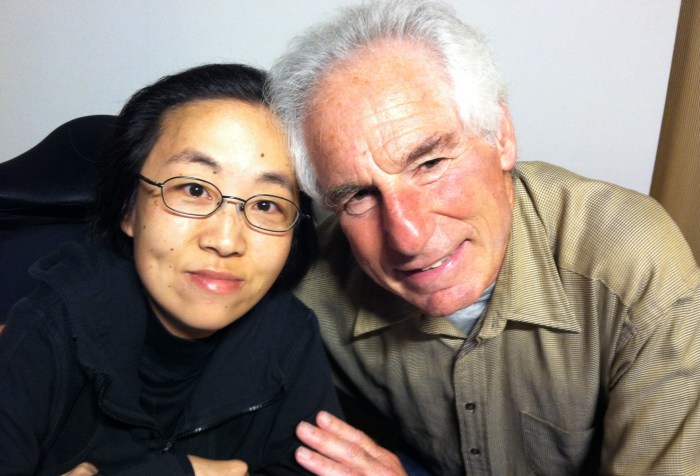 Asian American woman in a black hoodie and in a wheelchair sitting on the left side. Next to her is an older White man with white hair.