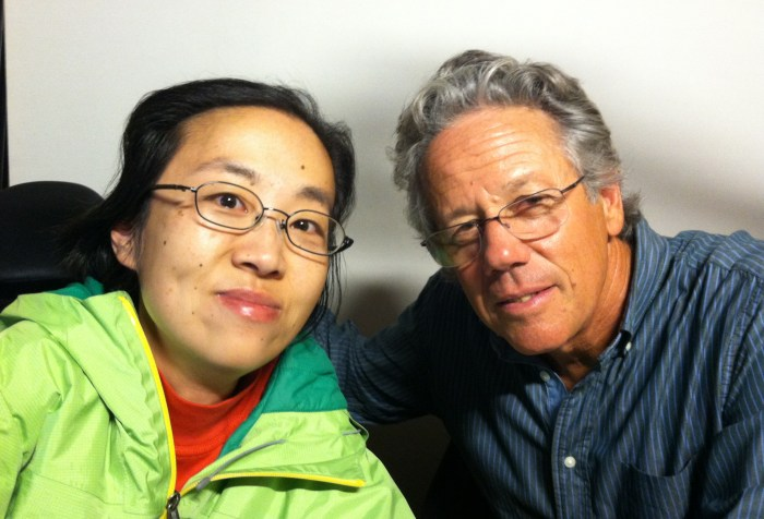 Asian woman sitting on the left-hand side wearing glasses and a green jacket. Next to her is an older white man with curly hair and glasses. He is wearing a blue shirt