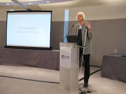 A woman with white hair and a gray blazer with black pants standing at a lectern. She is holding a white cane and screen is to the left of her showing a slide.