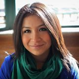 Latina with dark brown hair wearing a blue sweater and a green and black scarf. She is smiling at the camera.