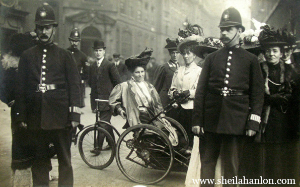 Black and white image of a woman reclining on a large tricycle that she uses due to her paralysis. She's surrounded by police officers.