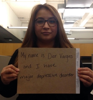 "Photo of a Latina with long brown hair and wearing glasses. She is holding a sign that reads: ""My name is Dior Vargas and I have major depressive order."""
