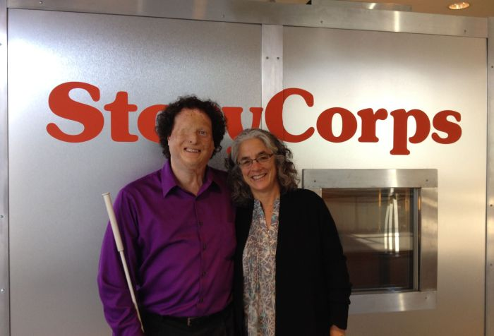 Picture of two individuals standing in front of a StoryCorps recording booth. A man is on the left side wearing a purple shirt and black pants. He is holding a cane The woman next to him has long white and dark hair and wears glasses. She is wearing a black cardigan sweater. Both are smiling at the camera.