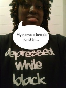 "Black woman with curly black hair with a caption bubble coming out of her mouth that says: ""My name is Imade and I'm…"" and she is wearing a black t-shirt that says, ""Depressed while black"""