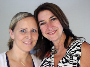 Image of two women smiling at the camera standing close to each other. On the left is a woman with blonde hair and blue eyes and on the right is a woman, her mother, with long brown hair and brown eyes