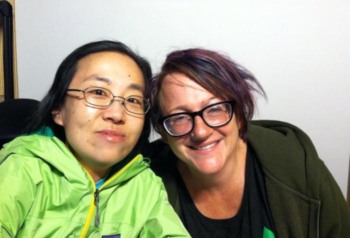 Two people smiling at the camera sitting side-by-side. On the left is an Asian woman wearing a green jacket and glasses. On the right is a white woman with brown hair with purple highlights and glasses.