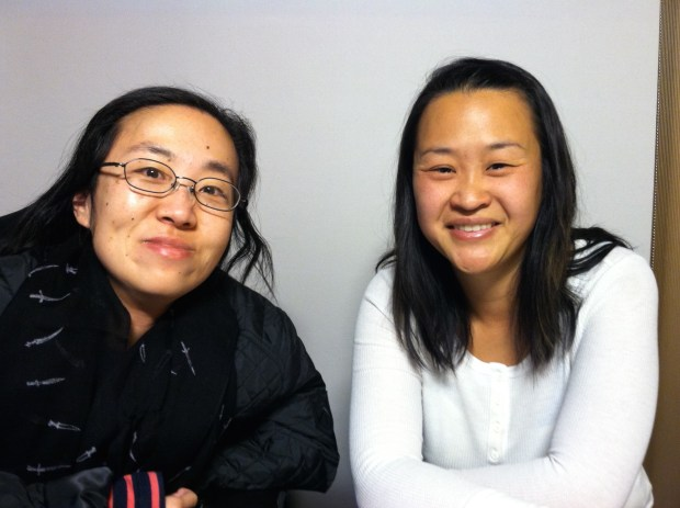 Two Asian American women sitting side-by-side smiling at the camera. The woman on the right is wearing a black jacket and glasses. The woman on the right is wearing a white shirt and has long black hair.