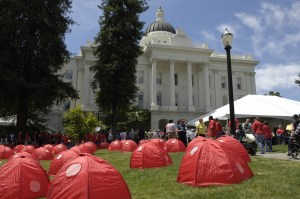 The capitol building in the background, Sacramento, California. In the foreground on a green grassy lawn are red tents throughout the lawn.