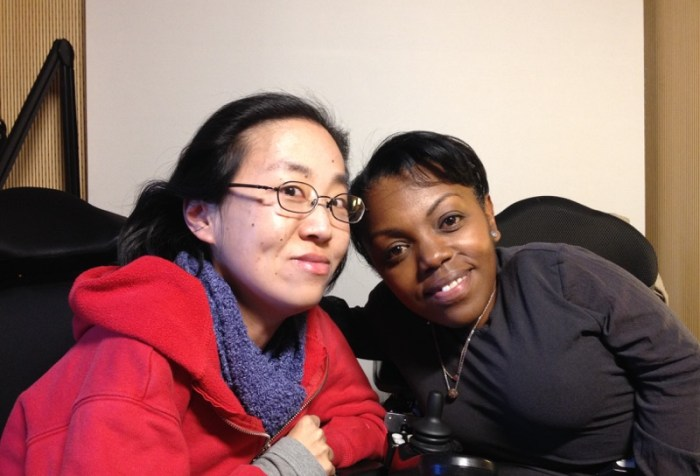 Image of two women in wheelchairs. On the left is an Asian woman with glasses and wearing a red hoodie. On the right is an African American woman with short black hair and a black shirt.