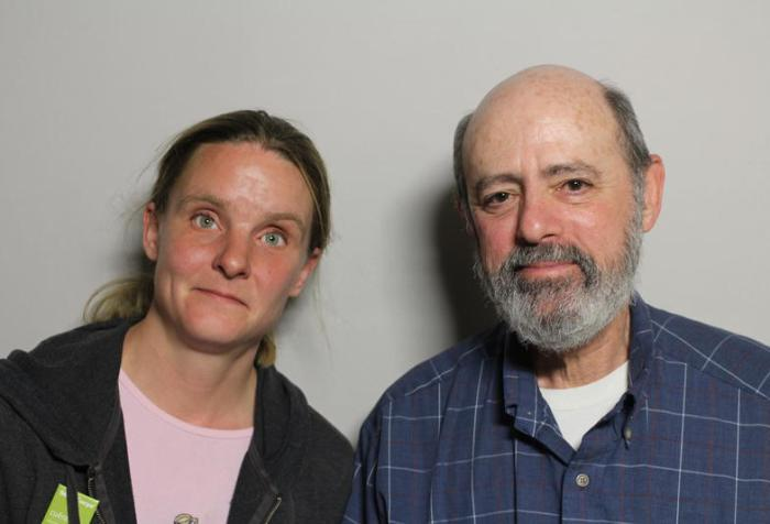 Image of two people standing next to each other. On the left is a young white woman with blonde hair tied back in a ponytail. She is wearing a black hoodie and pink t-shirt. To her right is an older white man with a gray beard. He is wearing a blue long-sleeved shirt.