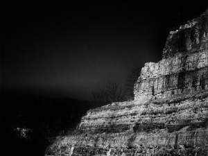"""""""Side of the Mountain.""""  Black and white image: a landscape of a mountain on the right side of the image with 3 ridges jutting out into the air in a stair-step formation. The left side of the image is dark sky."""