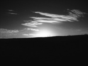 """Sunset."" Black and white image: a landscape image of the sun setting behind a hill, with a scattering of clouds overhead."