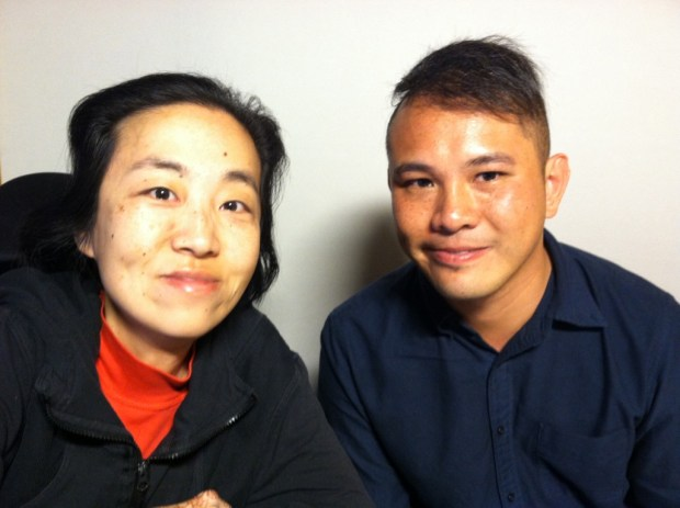 Photo of two Asian Americans. On the left is a middle-aged Asian American woman wearing a black hoodie and red turtleneck. On her right is a younger Asian American man with short hair and wearing a navy shirt.