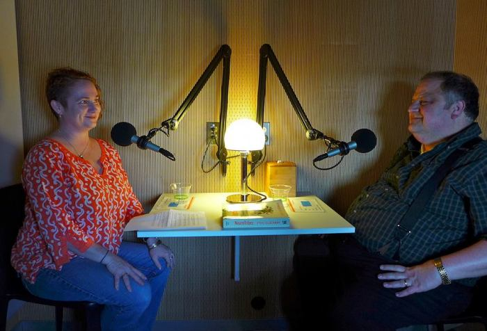 Image of two people facing each other in a recording booth with microphones in front of them. On the left is a middle-aged white woman with short red hair. She is wearing red-print shirt and blue jeans. On the right is an older white man with short brown hair. He is wearing a dark shirt with suspenders.