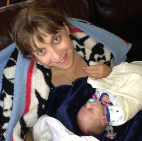 A young white woman with brown hair wrapped in a blanket with her newborn baby in front of her.
