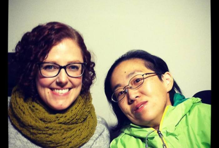 two women in wheelchairs sitting side-by-side against a plain white background. The white woman on the left has curly red hair and is wearing glasses, a gray sweater an a green scarf wrapped around her neck. The Asian American woman on the right has her head tilted toward her friend, she has black hair and is wearing glasses and a green jacket.
