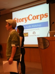 """Two people standing profile facing the left side of a room, in the backdrop is a projector screen with the words, """"StoryCorps"""" in large orange letters"""