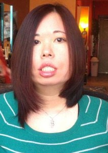 Photo of an Asian American woman with long straight hair. She is wearing a green sweater with white stripes and a necklace.