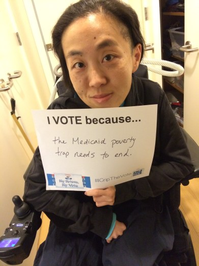 "Image of an Asian American woman in a wheelchair holding a white piece of paper that says, ""I Vote because...the Medicaid poverty trap needs to end."""