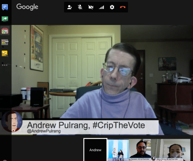 Screenshot of a Google hangout. A white middle-aged man with short brown hair with glasses. He is in a wheelchair and wearing a purple turtleneck. There is a horizontal panel below him that reads, Andrew Pulrang, #CripTheVote @AndrewPulrang