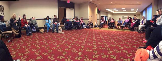 Photo of a wide view of a large meeting space with people with disabilities in a large circle.