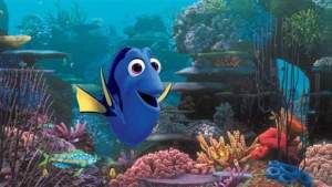 """An animated scene from the Pixar film """"Finding Dory."""" Dory, the central character who is a blue tang, in an underwater coral reef."""