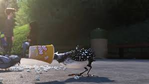 "An animated scene from the Pixar film ""Finding Dory."" A loon with black and white feathers with her head stuck inside a popcorn container"