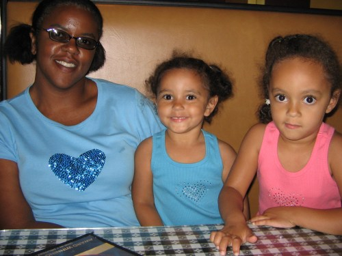 A young Black woman with hair tied in pig tails wearing a blue t-shirt. She is sitting at booth with two of her young biracial daughters, both are wearing tank tops with their hair tied back.
