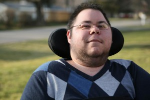 Photo of a man with short dark hair and glasses. He has stubble around his chin and neck. He is in a wheelchair with a black headrest behind him. He is wearing an argyle-print sweater in different shades of blue.