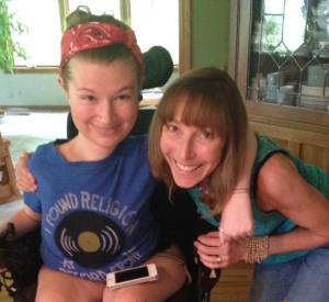 Photo of a young white woman in a wheelchair. Her hair is tied up with a red bandana. She has a blue t-shirt on, and an iPhone is on top of her left lap. She has her arm around a middle aged white woman who has shoulder-length blonde brown hair. She is wearing teal tank top and blue jeans. Both are smiling at the camera.