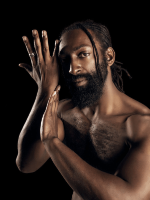 image of Antoine Hunter, a self-described handsome, dark milk chocolate, African American Man. He has long Ebony dreadlocks hair tied to back leaving one deadlock on the side of his face which is close to his eyes. He has a full 1-inch long Ebony-colored bread and full brown lips. He is bare chested and his right hand is to the side of his face with his left hand touching his right forearm. His eyes look straight at you with honest spirit.