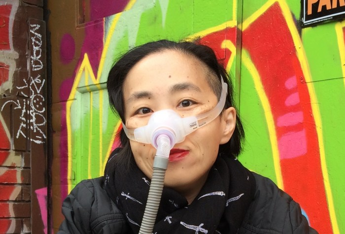 Asian American woman in a wheelchair. She is wearing a black jacket with a black patterned scarf. She is wearing a mask over her nose with a tube for her Bi-Pap machine. Behind her is a wall full of colorful street art