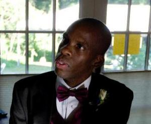 Image of Leroy Moore, a Black man with a shaved head looking left from the camera. He is wearing a black tuxedo with white shirt and magenta bow tie. Behind him is a glass-paned window.