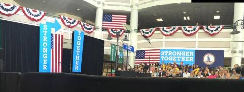 "Photo of the stage at George Mason University that has a lectern and signs that say, ""Stronger Together"". Patriotic bunting and American flags are in the background."
