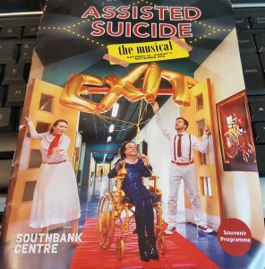 "Program from the theatre show, ""Assisted Suicide: The Musical"" featuring a white woman sitting in a gold wheelchair. On both sides are two people dressed in white and red guiding her down a red carpet. These people are holding helium balloons with spelling the word, ""Exit"""
