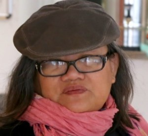 Middle-aged Asian woman with shoulder-length long hair, a hat on her head, and eyeglasses. She has a pink scarf wrapped around her neck.