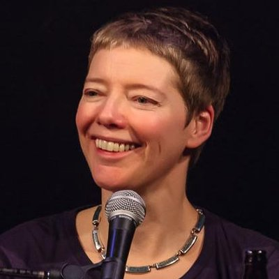A middle-aged white woman with short cropped hair. She is looking toward the left of the image with a microphone in front of her. The background is all black and she is wearing a scoop neck shirt with a metallic necklace.