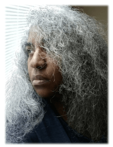 Image of an Afro-Latina woman with long curly gray hair. She is staring out at the window that has white blinds.
