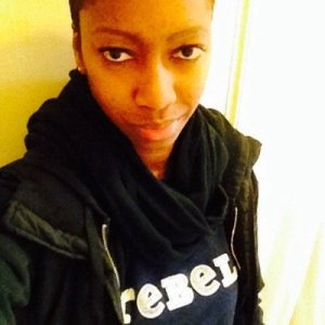 "TL , a black person with short hair takes a selfie while wearing a black hoodie & black scarf with a navy shirt that has white words ""REBEL."""