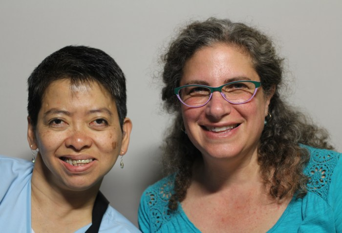 Image Description: A photo featuring Suzanne Levine and Yvette Fang taken on October 4th, 2014. The woman on the left is Yvette Fang. She appears to be of Asian descent, has short dark hair, is looking at the camera and smiling. She is wearing earrings and a light blue shirt. The woman on the right is Suzanne Levine. She appears to be white, has long curly brown hair that is pulled back in a half ponytail and is wearing glasses and an aqua colored shirt. She is looking at the camera and smiling.