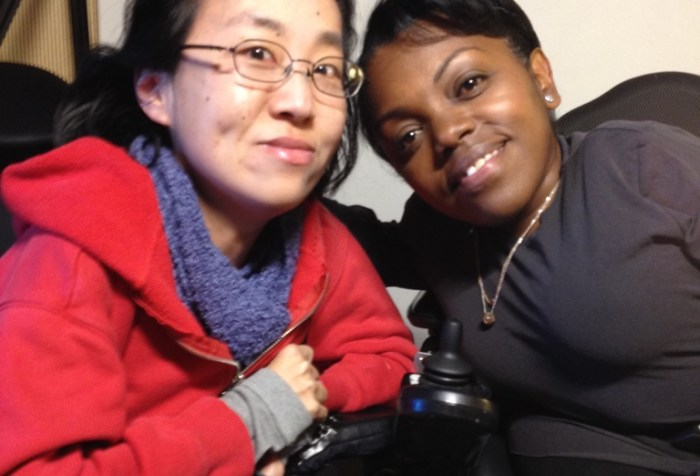 A photo featuring Yomi Wrong and Alice Wong taken on April 11, 2015. On the left is an Asian American woman in a wheelchair wearing a red hoodie and purple scarf. She has black hair, eyeglasses on, and a smartphone in her hand. On the right is a Black woman with short hair who is in a wheelchair. She is wearing a long-sleeved black shirt and a gold necklace. Both are smiling at the camera.