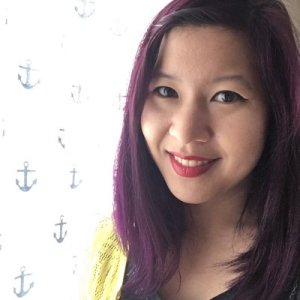 Photo of Elea Chang, a smiling Asian woman with shoulder-length purple hair and a yellow cardigan looking directly at the camera. She is to the right of the frame, in front of a white curtain patterned with blue anchors.