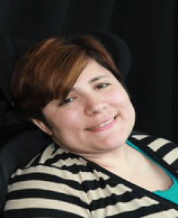 Black background of a light skinned woman with brown hair with gold streaks, brown eyes, sitting in her wheelchair wearing an aqua green undershirt and a beige and black striped sweater.